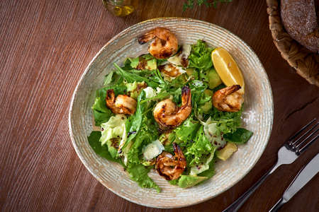 Fresh salad bowl with shrimp, avocado and arugula on wooden background close up. Healthy food. 写真素材