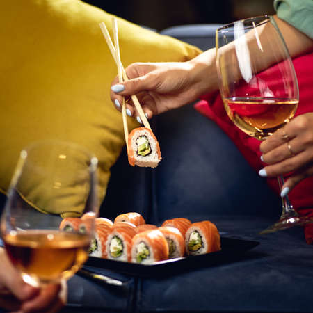 Sushi roll Philadelphia with salmon, smoked eel, avocado, cream cheese on the sofa. couple with glasses of wine. Japanese food