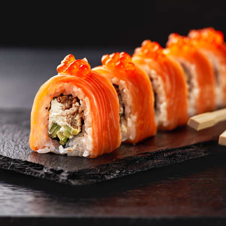 Japanese cuisine. Salmon sushi roll in chopsticks on a stone plate over concrete background. 스톡 콘텐츠