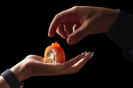 sushi roll on a female palm on a black background food concept