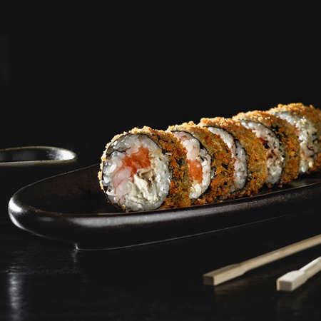 Hot fried sushi roll with salmon. Sushi menu. Japanese food. Hot fried sushi roll on black background 스톡 콘텐츠
