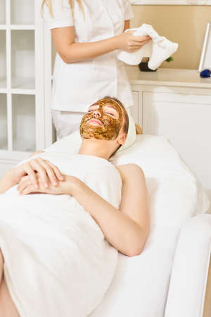 Young woman having face treatment in spa salon, facial scrub for face