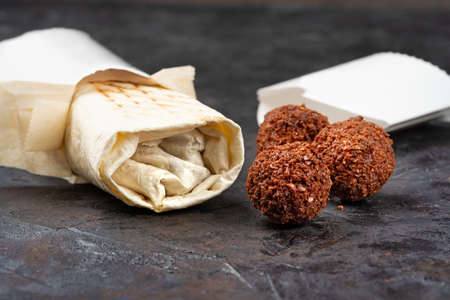 traditional oriental shawarma with fried falafel cutlets on a black background. Healthy snacks or takeaway lunch. concept of eco-packages for recyclable materials. Copy space