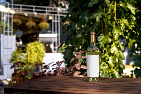 Drink, alcohol concept - Wine bottle on wooden table of restaurant terrace. Blank label for your text or logo. mock up Stock Photo