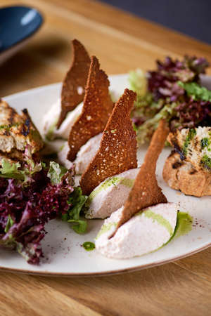 Healthy appetizer with cod liver, ricotta, croutons in a ceramic plate over. Healthy vegan food, clean eating, dieting, closeup