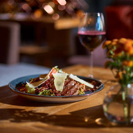 Warm salad with grilled veal, tomato, eggplant and glass of red wine on the table at restaurant