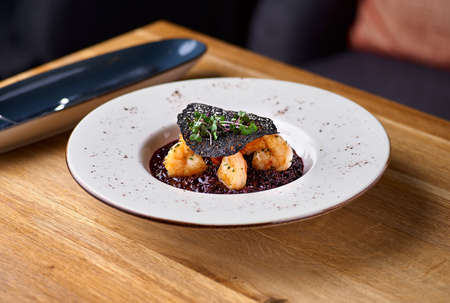 Black rice risotto. Shrimp risotto on a white plate on the table, serving in a restaurant, menu food concept Banque d'images