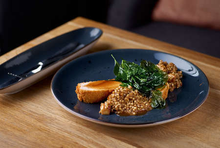 Chicken fillet with green buckwheat and porcini mushrooms on the table, in a restaurant, menu food concept.