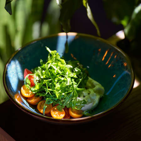 Italian fresh cheese Burrata with colorful cherry tomato salad, arugula and basil with pesto sauce on the table, serving in a restaurant, menu food concept.