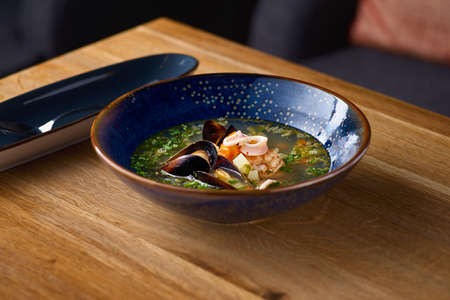 Delicious Seafood soup with seafood, shrimps and mussels on a wooden table