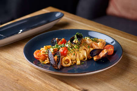 Pappardelle pasta with seafood, mussels and tomatoes. Italian Cuisine