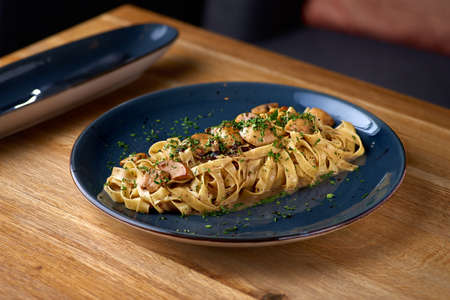 pasta with mushrooms and parmesan cheese on the table, serving in a restaurant Banque d'images
