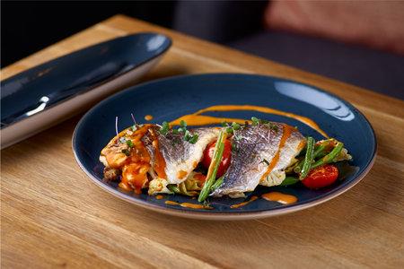 Sea food. Dorada baked with vegetables in shrimp sauce