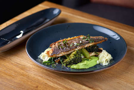 Grilled sea bass with broccoli and pea puree on a wooden table