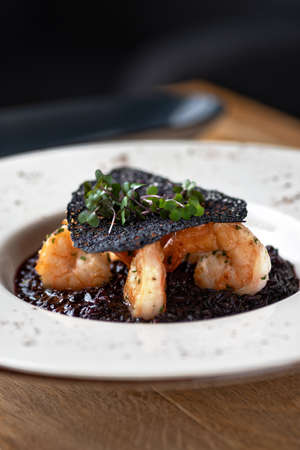 Black rice risotto. Shrimp risotto on a white plate on the table, serving in a restaurant, menu food concept.