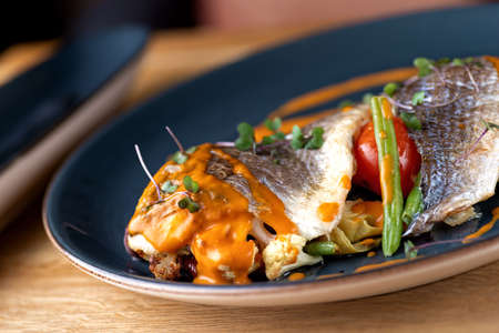 Sea food. Dorada baked with vegetables in shrimp sauce on the table, serving in a restaurant, menu food concept