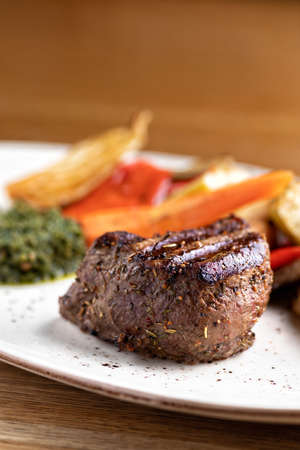 fillet of Mignon on a black plate on a background of greens, spices and vegetables, on a copper sheet. close up.