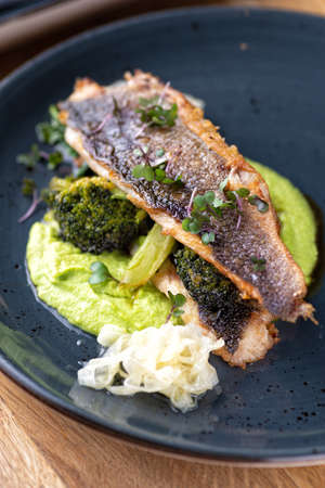 Grilled sea bass with broccoli and pea puree on the table, in a restaurant, menu food concept. Healthy balanced diet.