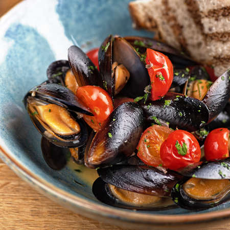 delicious italian fish dish made with mussels and white wine on the table, serving in a restaurant, menu food concept