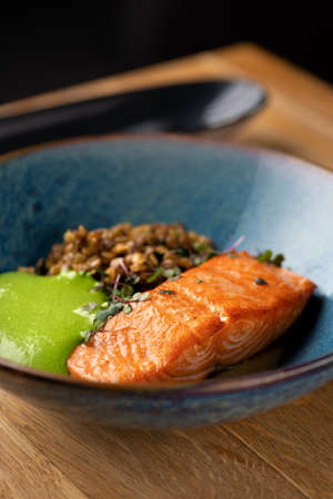 Baked Salmon with Green Lentilson the table, serving in a restaurant. Macrobiotic food concept. Healthy food