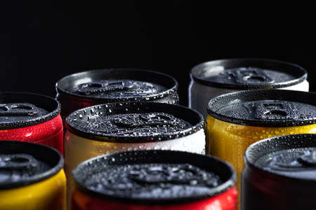 metal energy drinks cans on black background with water drops, copy space