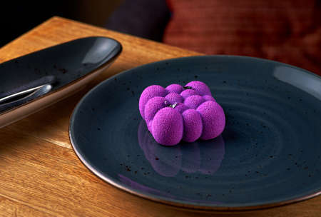 French Mousse Mini Desserts with Purple Velvet Cover on the table, serving in a restaurant, menu food concept.