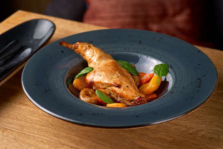 Tasty spicy rabbit stew in tomato sauce with white wine and herbs close-up on the table, serving in a restaurant, menu food concept. Banque d'images