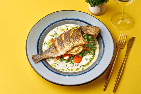 Close up of oven baked fish on on a yellow background. Healthy seafood.