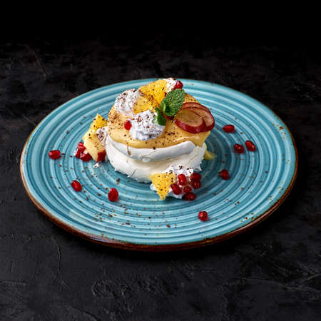 Anna Pavlova cake with lemon curd and fruits.