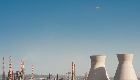 A plane flying over cooling towers and other gas pipes of an oil refinery plant
