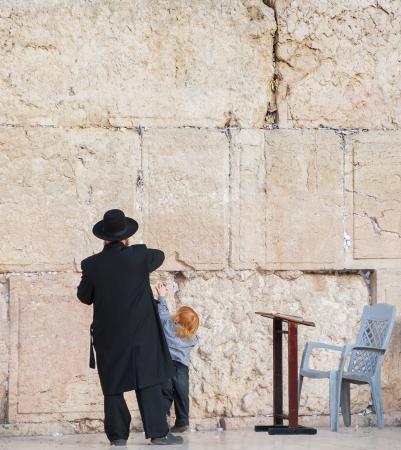 Rabbi and his little  son praying at the Wailing wall, Jerusalem, Israel  photo