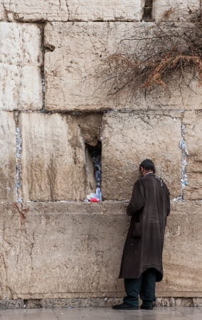 A man in rags standing by the Western wall. A lot of messages to god are stuck between the massive slabs of the Western wall.