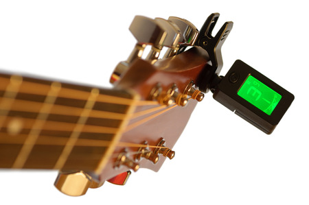 guitar tuner: Detail of acoustic guitar with guitar clip tuner. Very shallow dof.