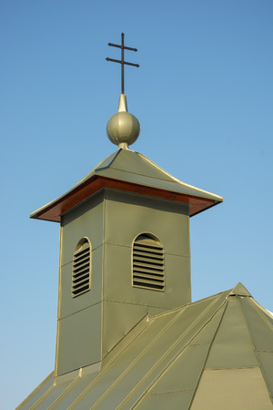 Detail of roof of chapel. Green building against clear blue sky Stock Photo