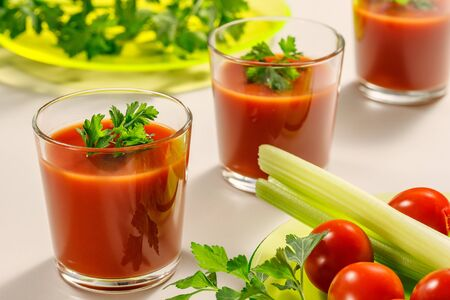 Three glasses of tomato juice decorated with parsley or coriander leaves. Next is a plate of parsley, tomatoes and celery stems Stock Photo