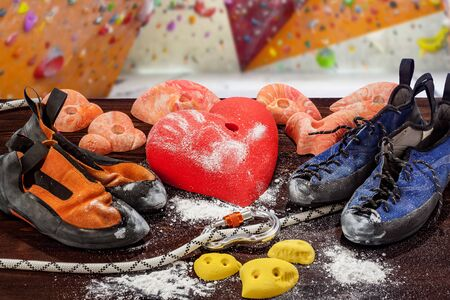 Two pairs of climbing shoes lie next to the climbing hook in the form of a heart. In the foreground, the rope passes through the carbine. In the background there is a climbing wall. Stock fotó