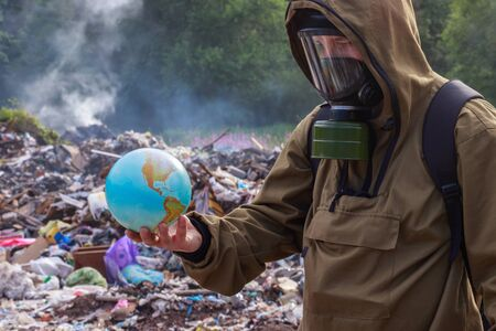 A man in a gas mask looks at the once beautiful planet earth. On the background of burning plastic trash. The concept of environmental problems — plastic garbage, illegal dumps, waste incineration Banco de Imagens