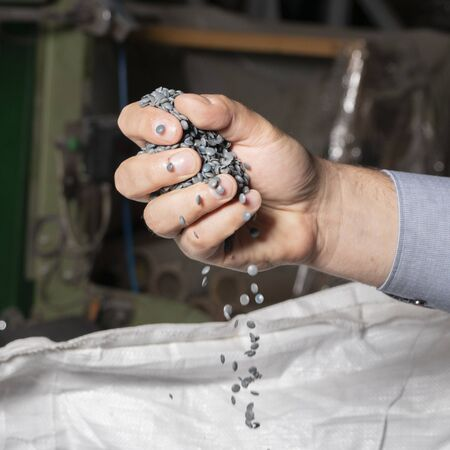 Grey pellets in his hand. Recycled plastic waste pellets. Raw materials for the production of plastic bags.