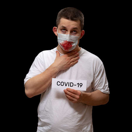 COVID-19 fear concept people in panic. Fear of contracting deadly disease with coronavirus COVID-19. Man coughs up blood from the lungs into medical mask. Infected with dangerous coronavirus infection Stockfoto