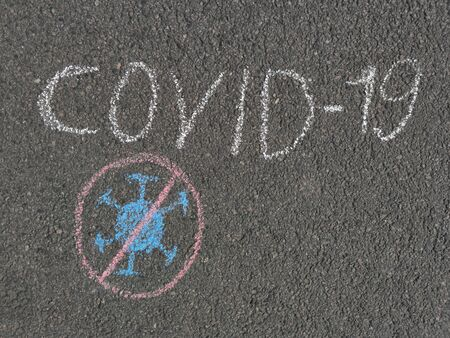 The concept away the coronavirus. The child drew a crossed-out coronavirus and the words COVID-19 on the asphalt with chalk. Drawing with chalk on the sidewalk covid19. Stop COVID-19