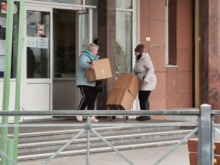 April 6, 2019, St. Petersburg, Russia: Women carry humanitarian aid from school. Helping parents in difficult situations during the coronavirus pandemic COVID-19. Food boxes Redactioneel