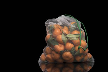 Tangerines in a reusable mesh bag Isolated black Stockfoto