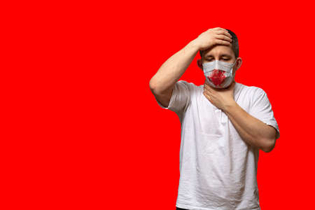 The World Health Organization WHO has said the coronavirus pandemic is on the rise worldwide. A man in a bloody surgical mask is sick with lung disease COVID-19. Red background. Stockfoto