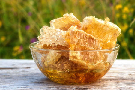 Honeycomb with golden honey in a glass bowl. Orange honey on an old rustic wooden table. The sun is shining on the honeycomb. Against the background of green grass, flowers bloom. Stockfoto
