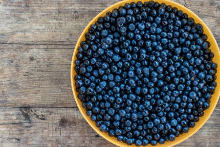 A bowl of blueberries on a rustic wooden table. Forest berries on an old table Stockfoto