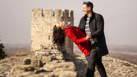 A couple in love dancing and jumping on a castle