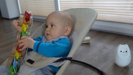 A cute baby playing with a wooden snake in a baby bouncer 4K