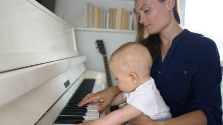 A cute mommy playing a white piano with her baby boy