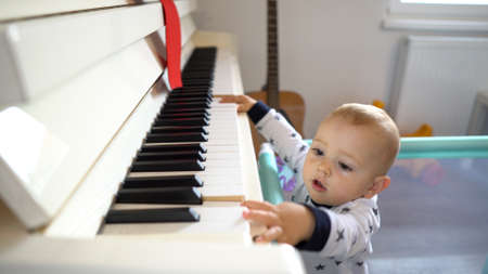 A cute baby boy trying to play a big piano while standing up. 4K