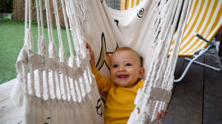 A cute baby boy smiling and swinging in a hammock outside.